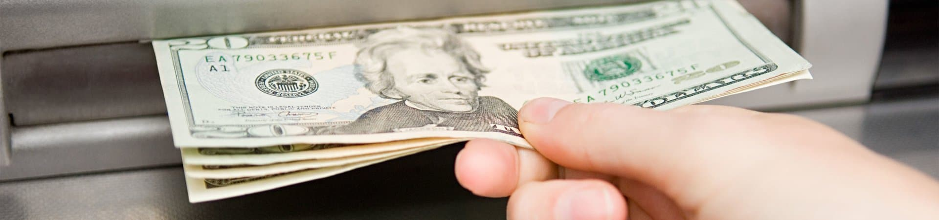 Hand Holding ATM America Profits